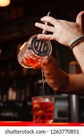 Brutal bartender pours Negroni cocktail