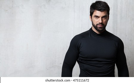 Brutal bearded athlete black blank T-shirt with long sleeves is against the background of a cement wall