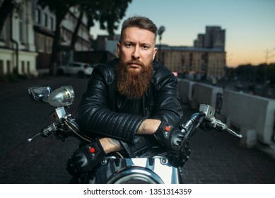 Brutal bearded biker poses on chopper, front view