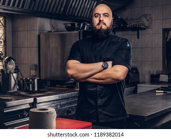 Brutal bearded chef cook in black uniform standing with crossed arms in the kitchen.