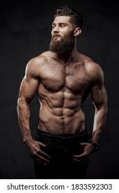 Brutaler Bärenkind mit nacktem Torso und Muskelaufbau mit Händen in Taschen, die auf dunklem Studiohintergrund stehen.