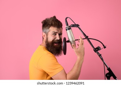 Brutal bearded guy singer with microphone on stage. Concert&music concept. Bearded man singing with microphone. Male lead vocalist singing in recording studio. Vocalist singing in condenser microphone