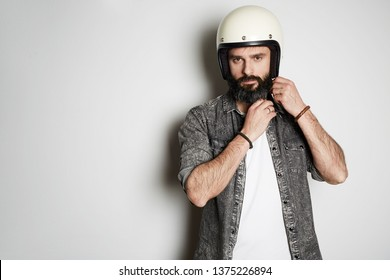 Brutal bearded hipster male model poses in black jeans shirt and blank white t-shirt premium summer cotton with moto helmet in hands, on white background. Copy paste Advertisement