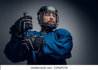 A brutal bearded ice-hockey player in safety helmet holds the gaming stick on grey vignette background.