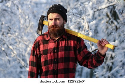 Brutal bearded lumberjack with ax in winter forest. Lumberjack with an ax in his hands. Male holds an ax on a shoulder. Brutal bearded man. Handsome man, hipster in snowy forest. Bearded lumberjack.