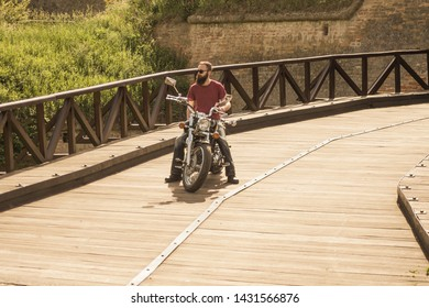 Brutal bearded male dressed in a red t-shirt and black pants sitting on his retro motorcycle at old town bridge