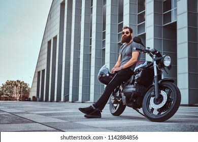 Brutal bearded male in a gray t-shirt and black pants holds a helmet sitting on his custom-made retro motorcycle against skyscraper.