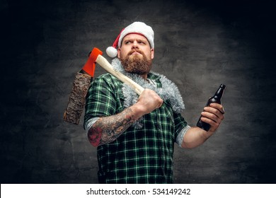 Brutal bearded male in Santa's hat wearing green plaid shirt, drinking beer and holds axe on a shoulder.