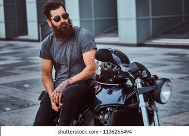 Brutal bearded male in sunglasses dressed in a gray t-shirt and black pants sitting on his custom-made retro motorcycle against a skyscraper.