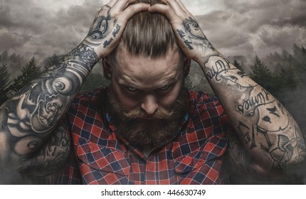 Brutal bearded male with tattooed arm looks down over cloudy sky.