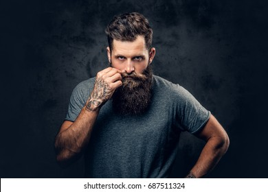 Brutal bearded male with tattoos on arms touches his moustache over grey background.