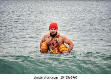 Brutal bearded man of 30-40 years with Slavic appearance, eupropeoid, floats in the sea with pumpkins, portrait. Halloween 2018