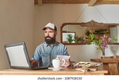 Brutal bearded man in cap using laptop with headphones and holding notepad while having morning snack and coffee.