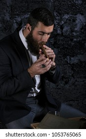 Brutal bearded man with cigar and whisky. Dark hair and beard wearing jacket. Against the wall.