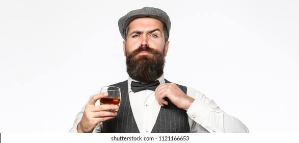 Brutal bearded man with glass of whiskey, brandy, cognac. Attractive man with a cognac. Old hipster style. Whiskey, brandy, cognac drink.