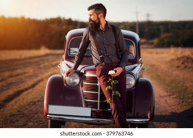 brutal bearded man with a mustache in a shirt, pants with suspenders stands leaning on the hood of a retro car holding a white rose and looking at the sunset