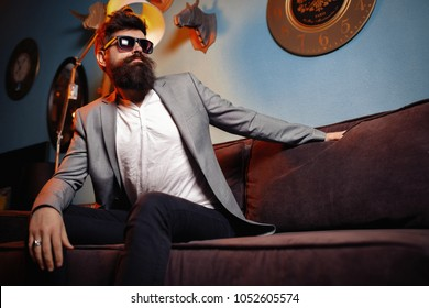 Brutal bearded man sitting in comfortable sofa. Handsome bearded man in suit on luxurious couch. Arrogant rich bearded man, sexy male, bisnessman.