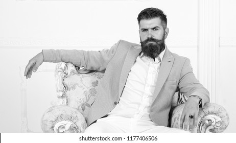 Brutal bearded man sitting in comfortable sofa. Handsome bearded man in suit on luxurious chair. Arrogant rich bearded man, sexy male, businessman. black and white