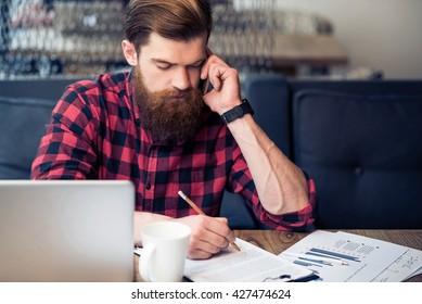 Brutal bearded man talking on cell phone