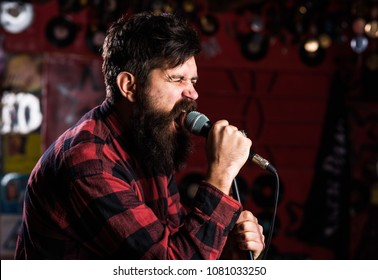 Brutal bearded singer with microphone on stage. Rock star concept. Guy likes to sing in aggressive manner. Man with tense face holds microphone, singing song, karaoke club background.