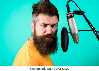 Brutal bearded singer with microphone on stage. Bearded man singing with microphone. Concert&music concept. Male lead vocalist singing in recording studio. Vocalist singing into condenser microphone.