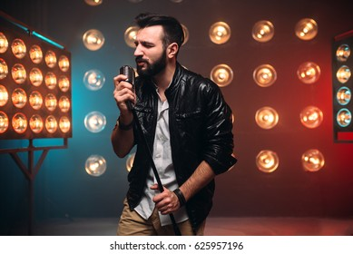 Brutal bearded singer with microphone on the stage