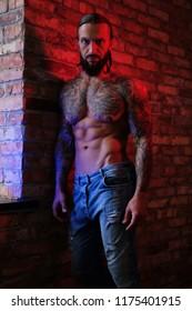 Brutal bearded tattooed male posing against brick wall.
