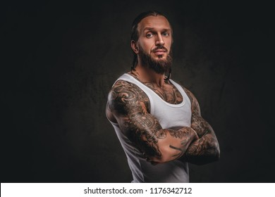 Brutal bearded tattooed male in white shirt posing with crossed arms. Isolated on a dark textured background.