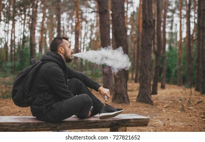 brutal bearded young man having rest in forest and vaping vape device. Lifestyle. Vape concept . Rest in forest