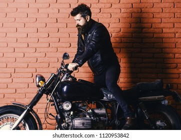 brutal biker on serious face in leather jacket gets on motorcycle. Man with beard, biker in leather jacket near motor bike in garage, brick wall background. Start of journey concept.