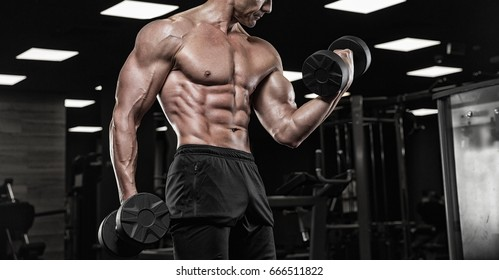 Brutal bodybuilder athletic man with six pack, perfect abs, shoulders, biceps, triceps and chest