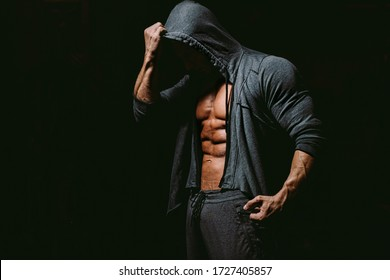 Brutal bodybuilder fitness model posing in gym on black background.  Fitness man wearing hoodie on naked body. Unidentified model showing six pack abs body