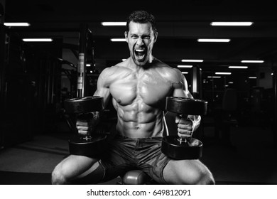 Brutal bodybuilder on diet resting and working out in the gym. Caucasian sexy fitness male model execute exercise with dumbbells