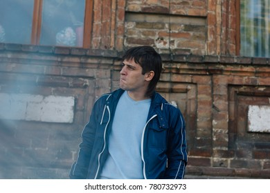 brutal bully boy walking in a summer Park. emotional portrait. problematic skin: acne and red spots. street style in clothes: ripped jeans and a sweater. long hair and a deep look