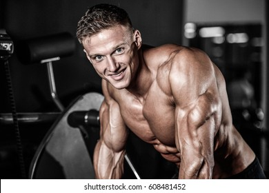 Brutal caucasian handsome fitness men on diet training triceps in gym pumping up body bodybuilding athlete