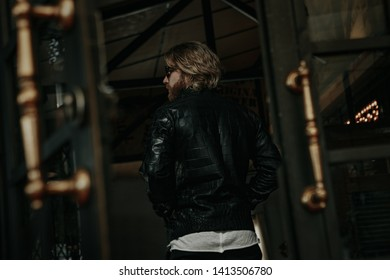 Brutal caucasian  man with long beard hipster in black leather jacket stay next to glass door