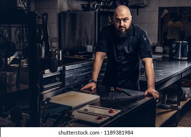 Brutal chef in black uniform leaning on a table and looking at camera in the kitchen.
