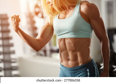 Brutal fitness blond with a muscular, straining biceps and abdominal muscles in the gym, part of the fitness body. Sports and fitness - concept of healthy lifestyle. Fitness woman in the gym.