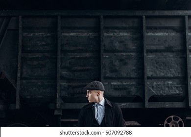 brutal gangster posing on background of railway carriage. england in 1920s theme. fashionable confident man. atmospheric moments. space for text