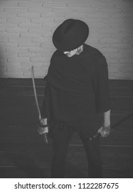brutal gangster in tattoos. Warrior in black hat and clothes, top view. Man with swords standing on wooden floor. Samurai, buddhist concept. Honor and dignity. Harakiri, suicide ritual.