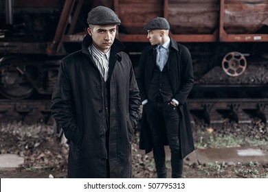 brutal gangsters posing on background of railway carriage. england in 1920s theme. fashionable confident man. atmospheric moments. space for text. peaky blinders