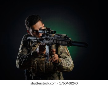 a brutal guy in military airsoft overalls poses with a weapon in his hands on a dark background