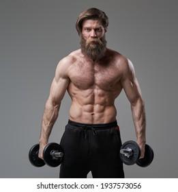 Brutaler Typ mit muskulär gebautem Aufbau auf grauem Hintergrund mit Hantel