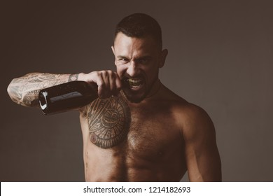 Brutal handsome latinos with tattooed body opens his teeth champagne. Champagne or wine bottle. Wine celebration concept
