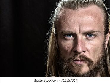 Brutal handsome man face. Close-up blonde nordic brutal man face on black background.