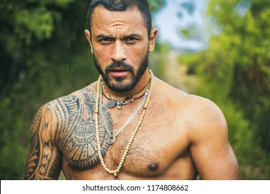 Brutal handsome man with tattooed body. Men tattoo casual fashion. Portrait of brutal handsome male model outdoor. Muscular athletic sexy male with naked torso.
