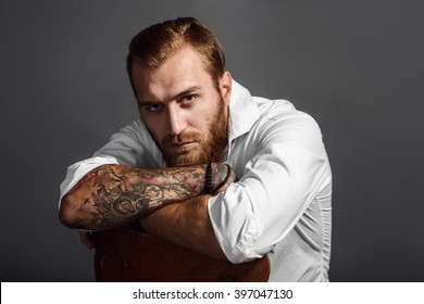 Brutal handsome man with tattooed body sitting on chair