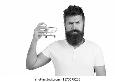 Brutal hipster man with beard holding small economical shopping cart. Choosing the best wine for dinner. Confident young man with beard hold shopping cart choosing wine. Shopping concept, supermarket