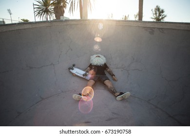 Brutal hipster man dressed up as santa claus lays on ground of skateboard pool after making tricks with longboard, summer vacation relax party time