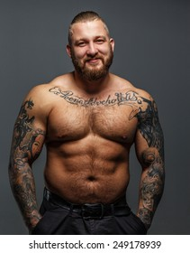 Brutal huge male with musculed body and tattooes smiling